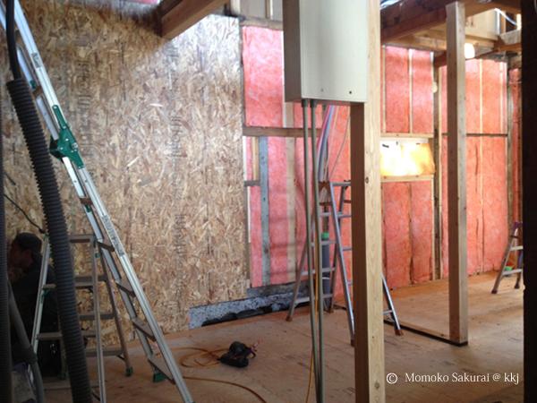 1階の壁の断熱工事。GWが入ったところ。どうしても壁量が不十分なところは軸内側から構造用合板で補強をする。(写真左)このあと垂木下地をして、さらに50mmGWを付加して気密を取る。