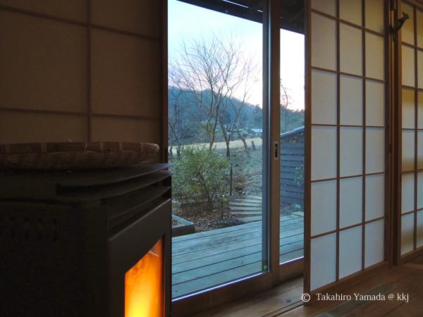 暖かな室内から冬枯れの里山を望む