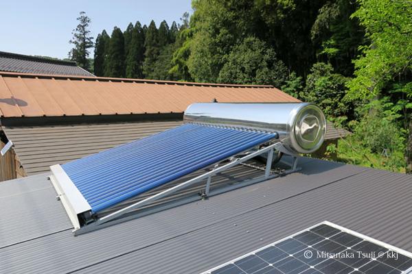 写真3:井戸小屋の屋根に乗せた真空管式太陽熱温水器と太陽光発電0.3kW(手前)