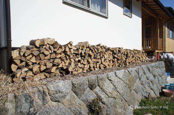 軒下の野積みの薪置き場-石垣の上なので排水が良好